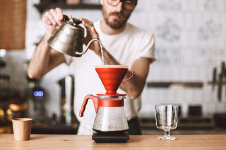 Close up photo of barista standing at counter and preparing pour over coffee in cafe. Standard-Bild