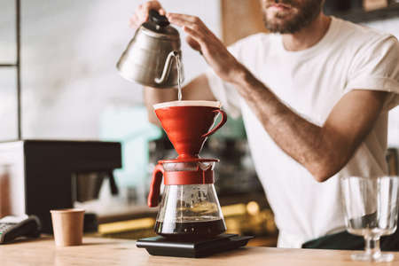 Close up photo of barista at bar counter preparing coffee in pour over and hario style while working in cafe.