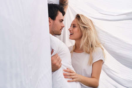 Young brunette man with pillow in hand dreamily looking at beautiful smiling blond woman lying together under blanket in bed at cozy home