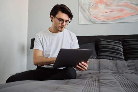 Young handsome brunette man in T-shirt and eyeglasses sitting on big bed at modern home thoughtfully working on laptop alone Stock fotó