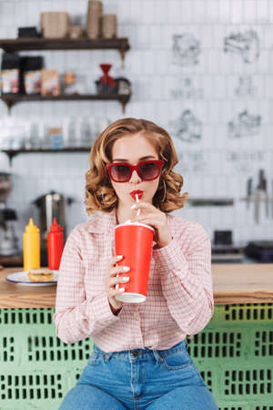 Pretty lady in sunglasses and shirt sitting at the bar counter and drinking soda water while spending time in cafe.