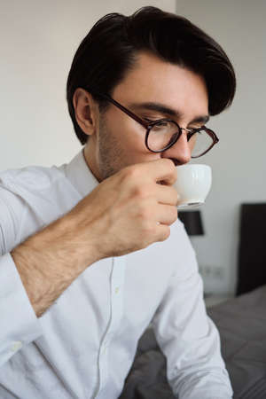 Close up photo of young attractive brunette man in white shirt and eyeglasses sitting on bed dreamily drinking coffee in hotel