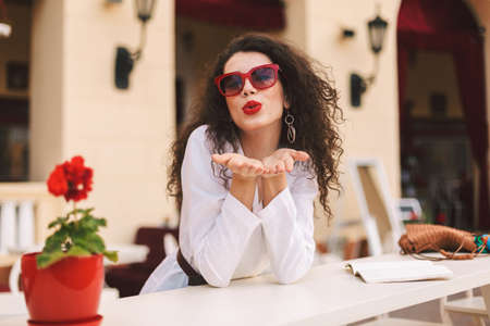 Pretty lady with dark curly hair in sunglasses standing and dreamily sending air kiss in camera, while spending time in summer terrace of cafe 版權商用圖片