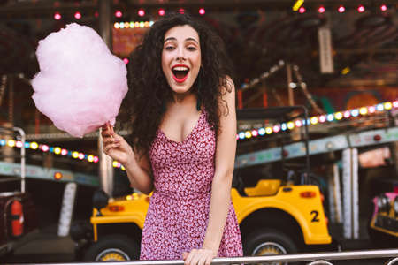 Pretty woman with dark curly hair in dress standing with cotton candy in hand, and happily looking in camera while spending time in amusement park with attractions on background