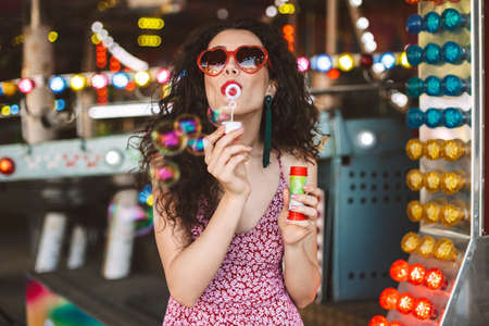 Beautiful lady in heart sunglasses and dress standing and blowing bubbles while spending time in amusement park.