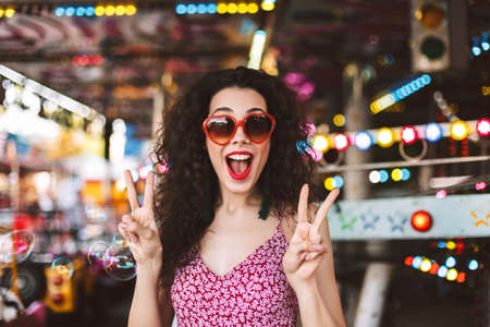 Young smiling lady in heart sunglasses and dress standing, and happily looking in camera while showing two fingers gesture in amusement park