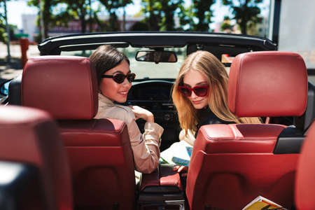 Beautiful girls in sunglasses happily looking in camera spending time together driving cabriolet car on city streets outdoor Standard-Bild