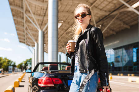 Beautiful girl in sunglasses and leather jacket, dreamily looking in camera holding coffee to go in hand near airport with black cabriolet car on background