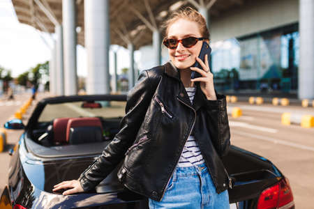 Beautiful smiling girl in sunglasses and leather jacket leaning on black cabriolet car happily talking on cellphone with airport on background