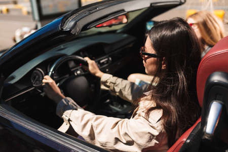 Beautiful girls in sunglasses from back spending time together driving cabriolet car on city streets outdoor