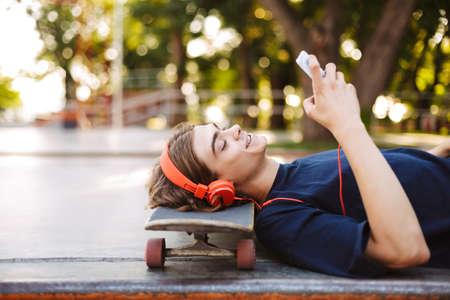 Portrait of young guy in orange headphones lying on skateboard happily using cellphone spending time at skatepark