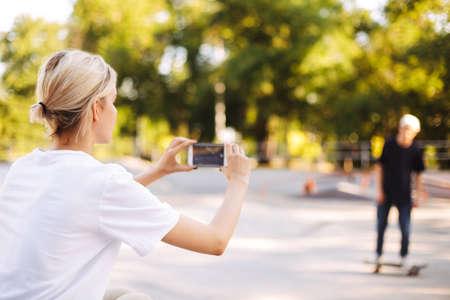 Cool girl recording new video on cellphone of young skater on skateboard for vlog spending time at skatepark