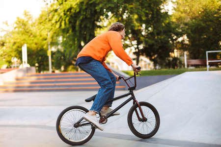 Young guy in orange pullover and jeans from back riding bicycle at modern skatepark