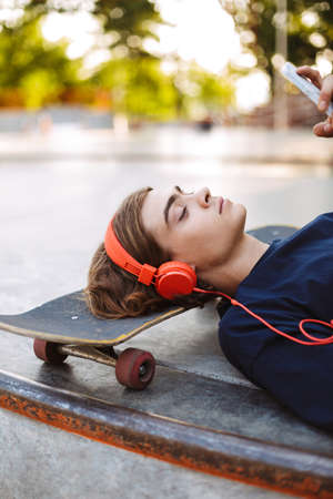Close up thoughtful guy in orange headphones lying on skateboard using cellphone at skatepark