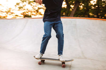 Close up skater boy in black T-shirt and jeans practicing at modern skate park 스톡 콘텐츠 - 147922971
