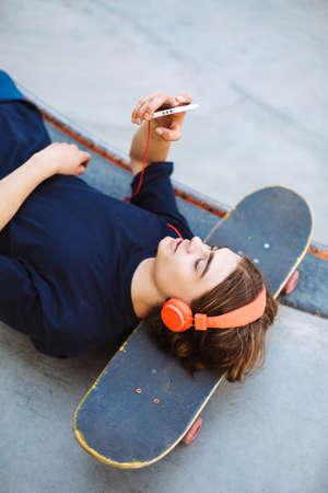 Young guy in orange headphones lying on skateboard dreamily using cellphone spending time at modern skatepark