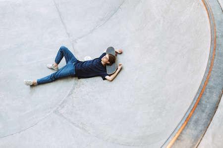 Young guy dreamily lying on skateboard in empty bowl at modern skatepark