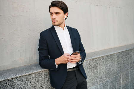 Young attractive serious bearded brunette man in white shirt and classic suit with wireless earphones holding cellphone in hand thoughtfully looking aside on street