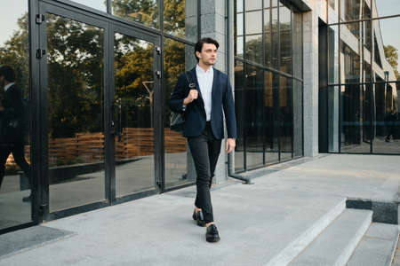Young attractive bearded brunette man in white shirt and classic suit with wireless earphones and backpack on shoulder thoughtfully looking aside walking outdoor