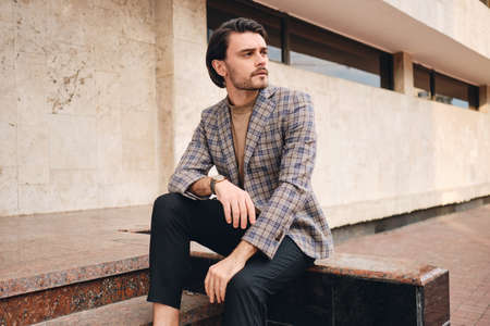 Young handsome serious man in stylish checkered jacket thoughtfully looking away outdoor