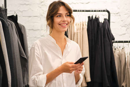 Young pretty woman happily using cellphone working in modern fashion showroom