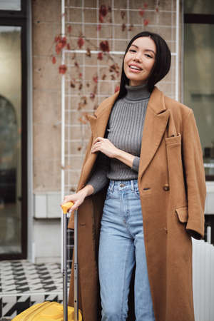 Attractive smiling stylish Asian girl in coat happily looking in camera with yellow suitcase on city street Stockfoto