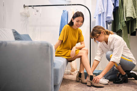 Young fashion consultant helping trying on boots to pretty smiling Asian girl in modern showroom