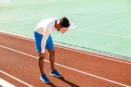 Young exhausted African American sportsman made a stop during run on racetrack at city stadium