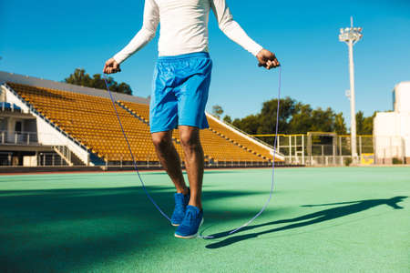 Close up African American sportsman jumping on skipping rope during workout at city stadium