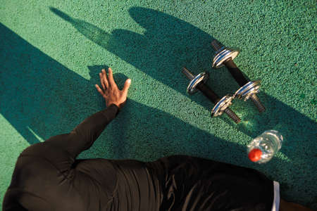 Close up sportsman resting after workout with dumbbells outdoor