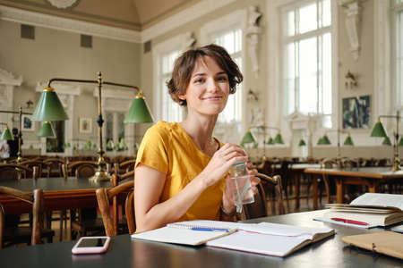 Young pretty smiling female student with water in hand joyfully looking in camera during study in library of university