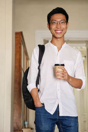 Young attractive smiling asian male student in eyeglasses with backpack and coffee to go joyfully looking in camera in university