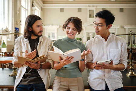Group of young multinational students happily studying with book and making notes together in library of university Stockfoto