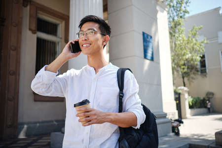 Young casual asian male student in eyeglasses with backpack happily talking on cellphone on street near university