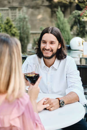 Young attractive brunette bearded man in shirt with glass of winejoyfully looking at girlfriend on romantic date in cafe outdoor