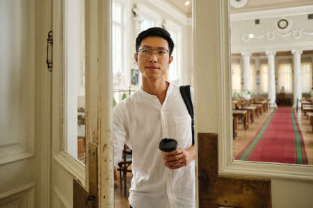 Young attractive asian male student in eyeglasses with coffee to go opening library door in university