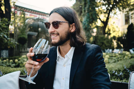 Young handsome smiling brunette bearded man happily drinking red wine in restaurant outdoor