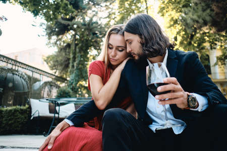 Young sensual couple with glass of red wine on date in restaurant outdoor