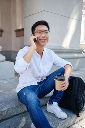 Young cheerful asian male student in eyeglasses with backpack happily talking on cellphone near university Banque d'images