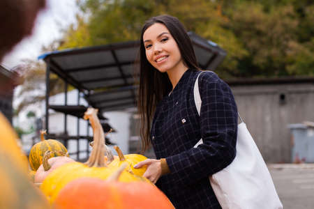 Young pretty casual woman happily looking in camera buying pumpkin for Halloween day at autumn farm shop outdoor