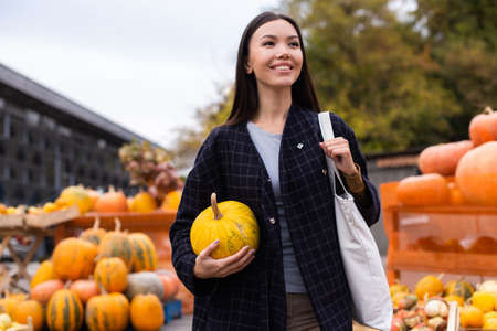 Young beautiful casual woman with pumpkin happily looking away at autumn farm shop outdoor