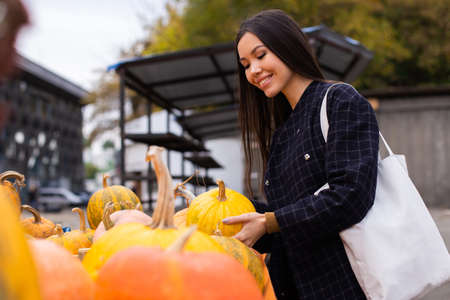 Young attractive casual woman happily buying pumpkin for Halloween day at autumn farm shop outdoor
