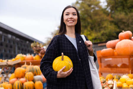 Young attractive casual woman with pumpkin joyfully looking away at autumn farm shop outdoor Banque d'images