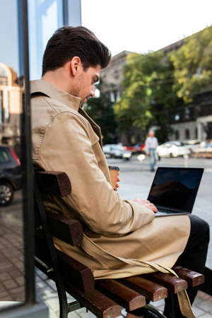 Back view of young stylish businessman in trench coat sitting on bench confidently working on laptop on city street