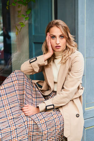 Attractive casual blond girl in stylish trench coat and skirt thoughtfully looking in camera outdoor