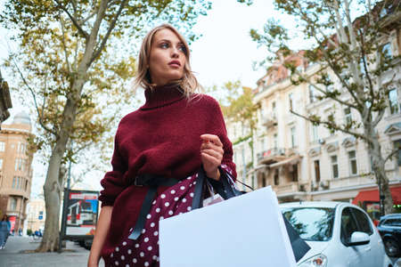Gorgeous stylish blond girl with shopping bags thoughtfully looking away on city street Zdjęcie Seryjne
