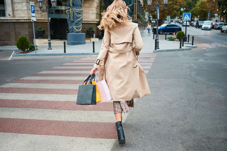 Back view of stylish blond girl with shopping bags walking on pedestrian crossing