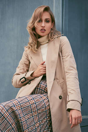 Beautiful serious casual blond girl in stylish trench coat sensually looking in camera outdoor Reklamní fotografie