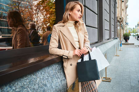 Side view of stylish blond girl in beige coat with shopping bags looking away on city street Stock fotó - 148182183