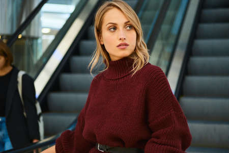 Portrait of beautiful blond girl in knitted sweater confidently looking away on escalator in shopping mall Stock fotó